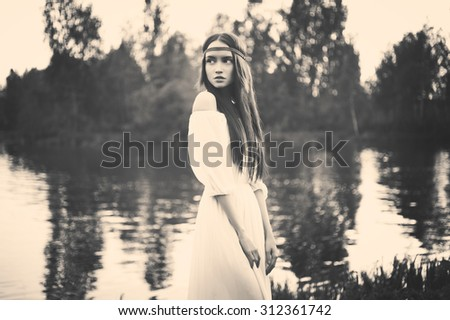Black and white outdoors fashion  photo of beautiful bohemian lady at river - stock photo
