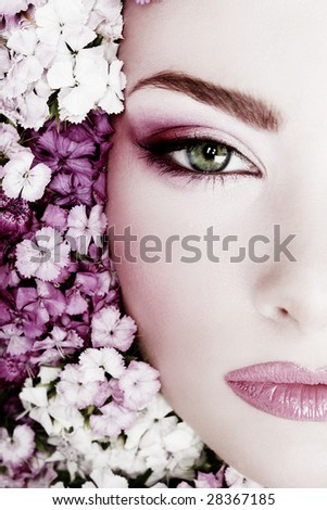 Black and white painted close-up portrait of girl with stylish makeup and flowers around her face - stock photo