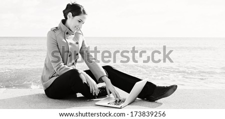 Black and white panoramic portrait of a young professional woman sitting down by the ocean with a sunny blue sky, using a laptop computer. Outdoors technology lifestyle. - stock photo