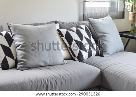 Black and white parallelogram pattern pillows on gray l shape comfy sofa - stock photo