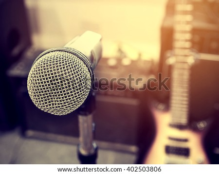 Black and white photo and lighting of The microphone in a recording studio or concert hall with amplifier and  electric guitar in out of focus background. : Vintage style and filtered process. - stock photo
