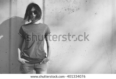 black-and-white photo of a attractive young woman dressed in a gray blank t-shirt posing against a background of a concrete wall in the rays of the setting sun - stock photo