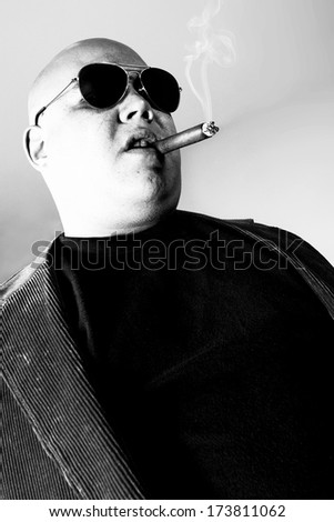 Black and white photo of a cigar smoking gangster.  Harsh lighting for more disturbing look.