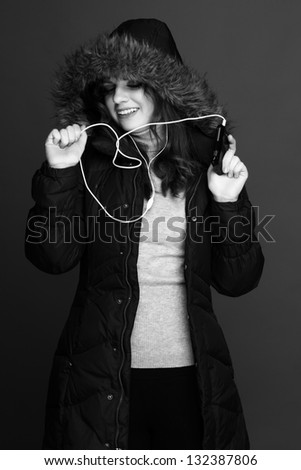 Black and white photo of a young cheerful girl with headphones on black background - stock photo