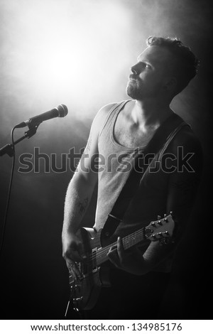 Black and white photo of a young man playing rock concert. sings and play guitar.