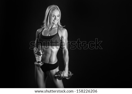 Black and white photo of athletic young woman doing a fitness workout with dumbbells on black studio background - stock photo