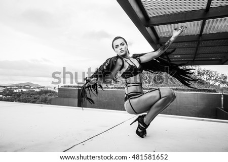 Black and white photo of beautiful seductive angel woman wearing lingerie and leather belts crouching on the roof over cloudy sky