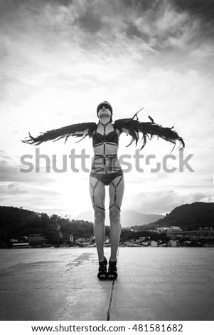 Black and white photo of beautiful seductive angel woman wearing lingerie and leather belts standing on the roof with wind in her wings over cloudy sky