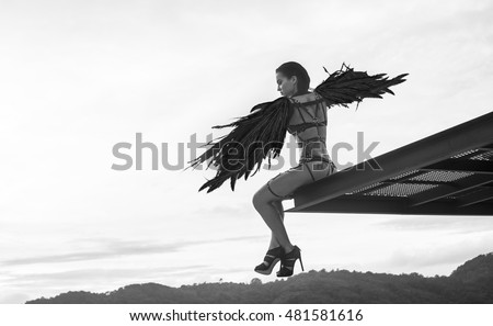 Black and white photo of beautiful seductive angel woman wearing lingerie and leather belts sitting on the roof edge with wind in her wings over cloudy sky