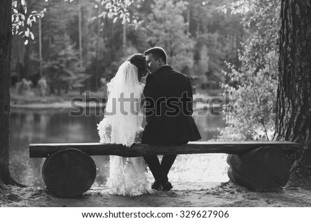 Black and white photo of bride and groom kissing on bench at riverbank - stock photo