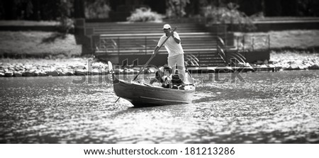 Black and white photo of bride and groom riding on gondola at park - stock photo