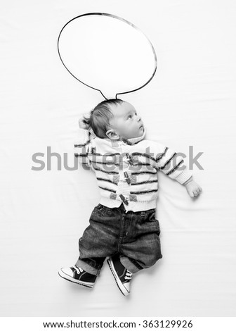 Black and white photo of cute baby boy with speech bubble lying on bed - stock photo