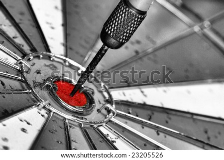 black and white photo of dart board with red bulls eye and dart in the middle.