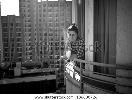 Black and white photo of depressed woman drinking coffee and smoking cigarette on balcony - stock photo