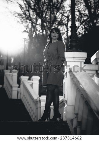 Black and white photo of elegant woman posing on stairs at park at sunny day - stock photo