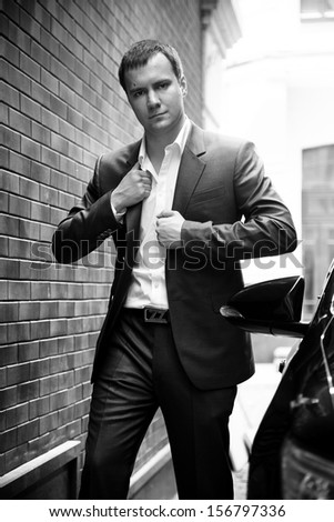 Black and white photo of handsome businessman standing on street near car - stock photo