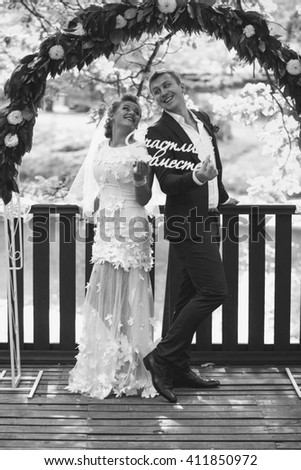 "Black and white photo of happy russian newlyweds posing with ""Happy together"" sign - stock photo"