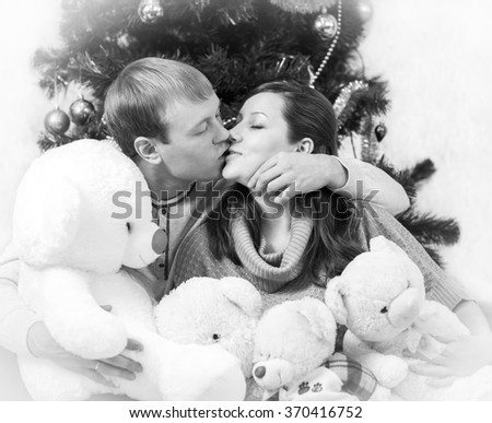 Black and white photo of kissing lovers with white vignette - stock photo