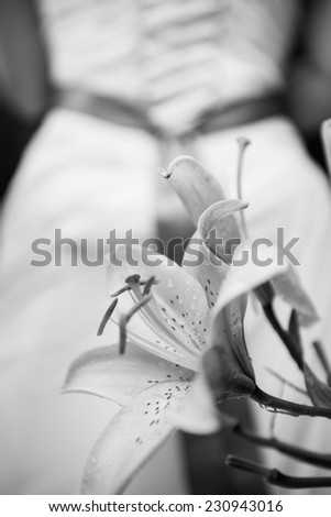 Black and white photo of lilly with bride in bridal gown in background - stock photo