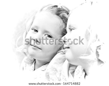 Black and white photo of little pretty girl looking in the mirror - stock photo