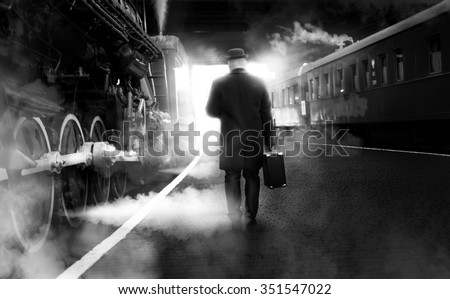 Black and white photo of man in vintage clothes walking on old railway station - stock photo