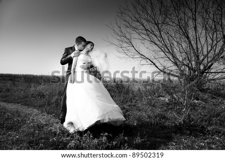black and white photo of newly married couple hugging in field - stock photo