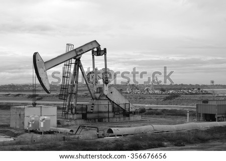 black and white photo of oil derrick with cloudy sky - stock photo
