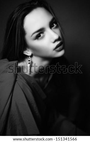 Black and White photo of pretty woman with beauty make-up and jewelry looking at camera