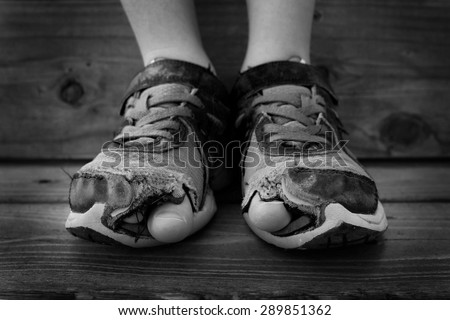Black and white photo of shoes with holes in them and toes sticking out child kid young - stock photo