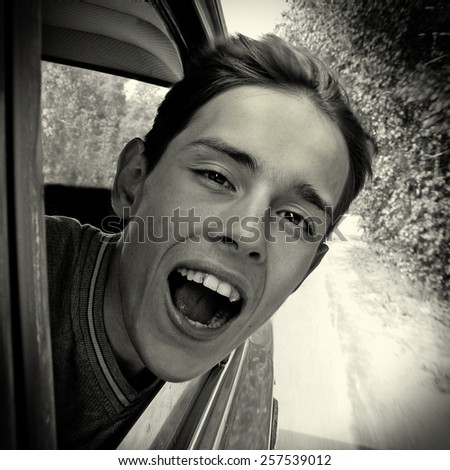 Black and White Photo of the Happy Teenager in the Car - stock photo