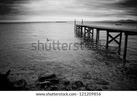 Black and white photo of the wooden jetty on a lake Garda in Italy - stock photo