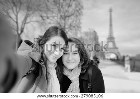 Black and white photo of two young woman taking a self portrait (selfie) near the Eiffel tower  - stock photo