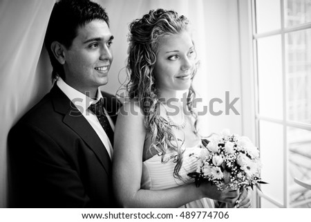 Black and white photo of wedding couple looking through the window