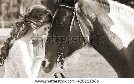 Black and white photo of young beautiful bride hugging a horse