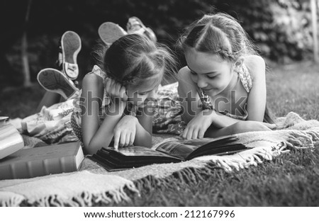 Black and white photo of young girls looking at family photo album - stock photo
