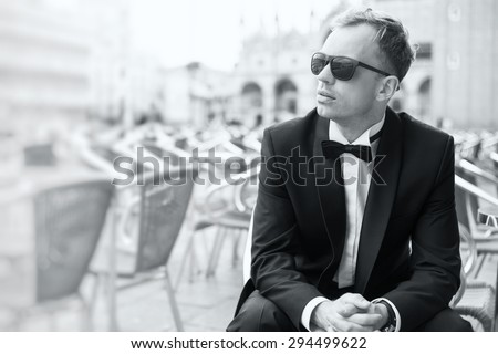 Black and white photo of young handsome man in tuxedo - stock photo