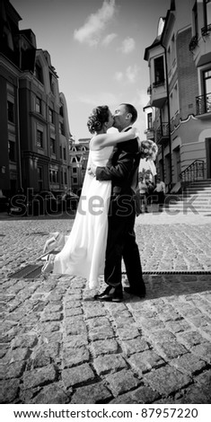Black and white photo of young newly married couple kissing outdoor - stock photo