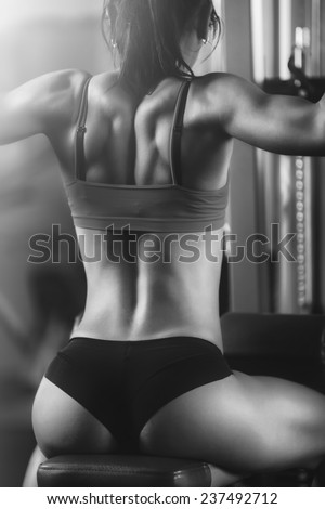 Black and white photo, strong fitness woman from behind. Brunette sexy fitness girl in sport wear with perfect body in the gym posing before training set. Attractive fitness woman, trained female body - stock photo