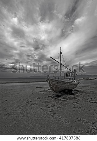 black and white photograph of a lone boat on the shore