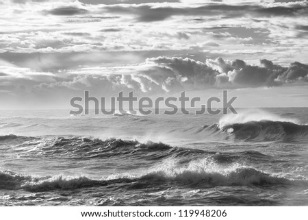Black and white photograph of a wave breaking beneath a storm sky - stock photo