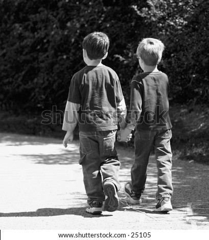Black and white photograph of friends walking away from camera, hand in hand - stock photo
