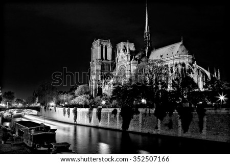Black and white photograph of Notre Dame Cathedral at night from the rear with a boat and a barge on the river Seine in Paris, France. - stock photo