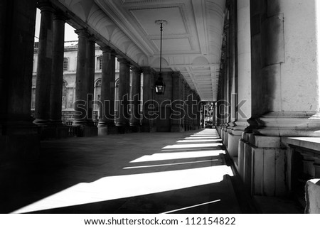 Black and white photograph of the sunlit corridor Royal Naval College Greenwich London England United Kingdom Europe UK - stock photo