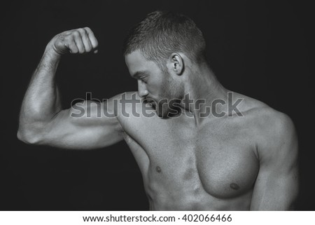 black and white photography. Model. Athletic guy with a naked body. The guy looks at his muscles. - stock photo