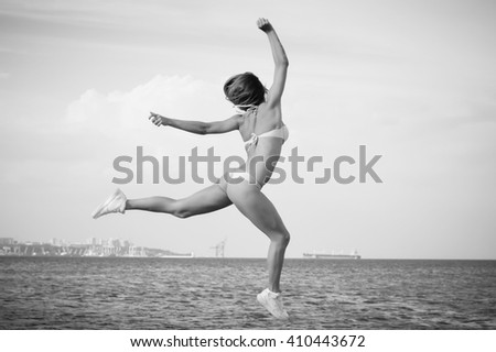 Black and white photography of amazing beautiful young lady enjoying dancing jumping over outdoors water sky background. Portrait of sporty girl - stock photo