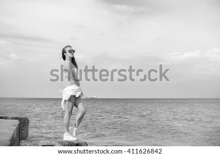 Black and white photography of beautiful young lady enjoying sea view on outdoors water sky background. Portrait of sporty girl - stock photo