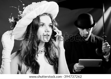 Black and white photography of beautiful young lady wearing hat and talking on mobile phone over male with tablet pc computer and umbrella  - stock photo