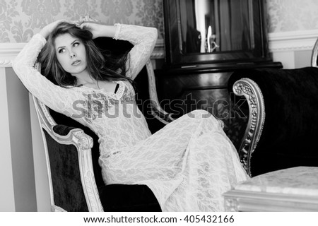 Black and white photography of beautiful young sexy woman relaxing on chair or couch and looking forward - stock photo