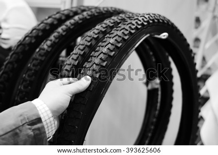 Black and white photography of hand choosing or presenting cycle spare tire. Close up