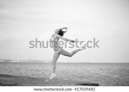 Black and white photography of jumping beautiful young lady, copy space background - stock photo